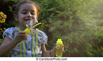 Slow motion of a Happy little caucasian girl blowing soap bubbles in on a sunny day. Concept happy childhood or children's games in nature.