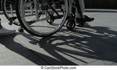 Slow motion of a kind person pushing a wheelchaired person -...