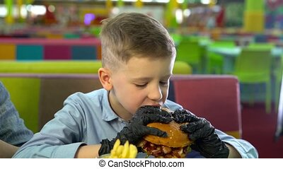 Slow motion of a little boy eating burger at restaurant. -...