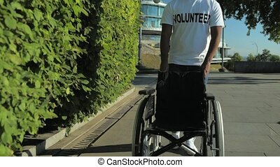 Slow motion of a pleasant volunteer pushing a wheelchair