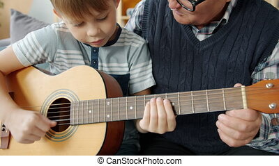 Slow motion of adorable child learning to play the guitar with grandad enjoying hobby and musical instrument at home. Family and leisure time concept.