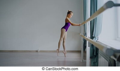 Slow motion of adorable girl ballet dancer in purple leotard...