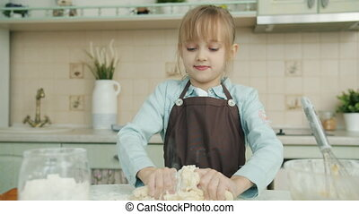 Slow motion of adorable little girl wearing apron mixing dough cooking pastry in kitchen at home concentrated on cookery. Childhood and food concept.