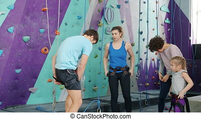 Slow motion of adults and kid putting on safety harness in rock-climbing gym talking wearing sports clothing. People, lifestyle and modern sports concept.