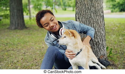 Slow motion of African-American girl caressing cute shiba...