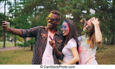 Slow motion of African American man in sunglasses taking selfie with pretty girls at Holi festival, their faces, hair and clothing are covered with paint.