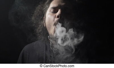 Slow motion of an adult man standing in a dark room alone vaping electronic cigarette and sending smoke steam circles towards camera