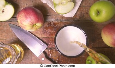 Slow motion of apple juice is poured into a metal cup of top view