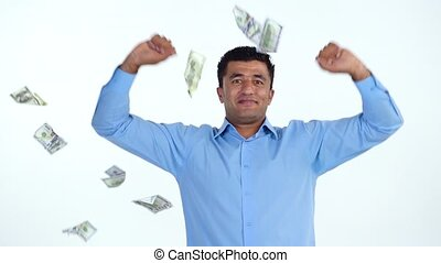 Happy arab man is delighted with the fact that a lot of dollar bills are fall on him. Slow motion