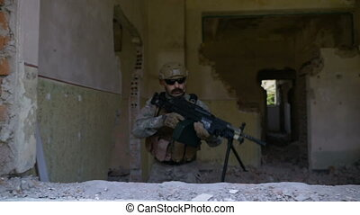 Slow motion of armed soldier in camouflage with machine gun...
