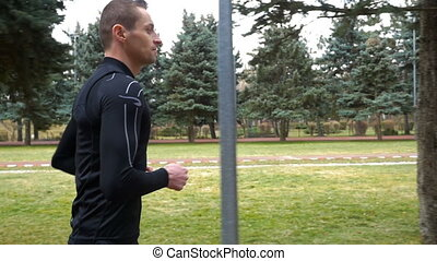 Slow motion of athletic man running in the park