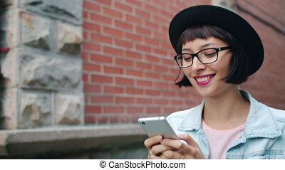 Slow motion of attractive girl looking at smartphone screen...
