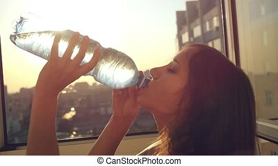 Slow motion of attractive woman drinking water at sunset city