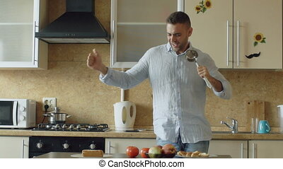 Slow motion of Attractive young funny man dancing and singing with ladle while cooking in the kitchen at home
