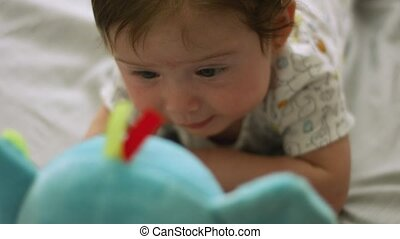 Slow motion medium shot of a baby doing tummy time in front of a stuffed animal