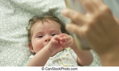 Baby lying down in bed and looking up at cell phone being held by mother