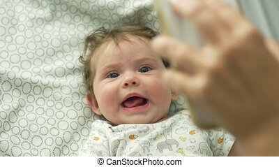 Baby lying down in bed and looking up at cell phone
