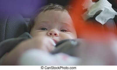 Slow motion close up shot of a baby moving in her car seat