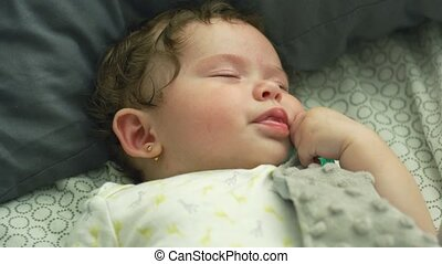 Slow motion shot of a baby lying down in bed and moving lips as she falls asleep