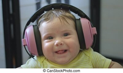 Slow motion shot of a baby wearing headphones and sticking tongue out and smiling