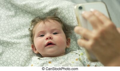 Baby lying down in bed and looking up at cell phone being held by mother and sneezing