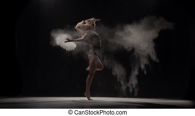 Slow motion of beautiful performer throwing dust particles in air.