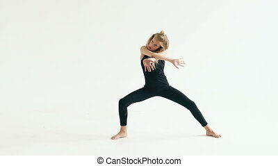 Slow motion of beautiful teenage girl dancer dancing contemporary on white background indoors