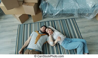 Slow motion of beautiful young family talking and gesturing lying on floor in new apartment enjoying relocation making future plans. People and conversations concept.