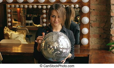 Slow motion of beautiful young woman with disco ball posing and smiling in studio indoors