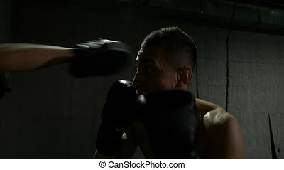 Slow motion of boxer training uppercut punches in boxing gym...