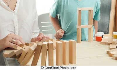 Slow motion of boy pushing wooden block and starting domino effect. Wooden blocks falling in chain. Concept of children education at home during lockdown and staying at home.