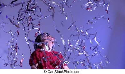 Slow motion of boy throwing up tinsel on gray background. -...