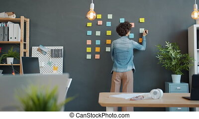 Slow motion of young businesswoman writing on paper sticky notes on wall working alone concentrated on creative job. People and corporate activities concept.