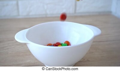 Slow motion of candies falling into glass bowl on pink background. 4k stock footage.