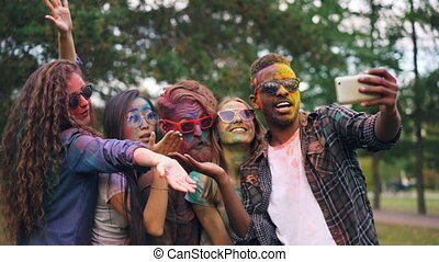 Slow motion of carefree students with coloured faces taking selfie with smartphone standing outdoors in park and posing for camera. Holi festival and photo concept.