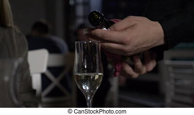 Slow motion of champagne poured in glass by waiter in a...