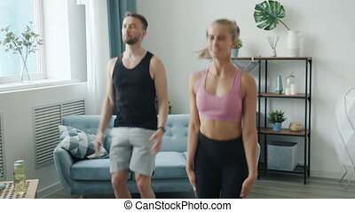 Slow motion of cheerful active youth in sports clothing training at home jumping enjoying exercise