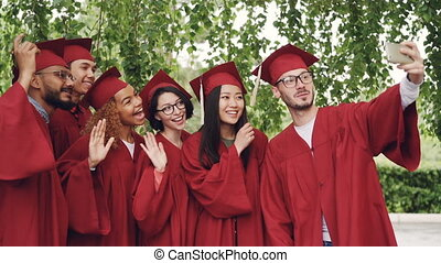 Slow motion of cheerful graduating students taking selfie with smartphone, young people are posing, showing hand gestures, making funny faces and laughing.