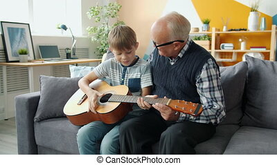 Slow motion of cheerful people grandson and grandfather playing the guitar at home, old man is teaching a boy to play. Musical instruments and lifestyle concept.