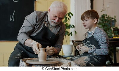 Slow motion of cheerful senior craftsman making vase on pottery wheel and talking to happy child grandson in workshop. Family and hobby concept.