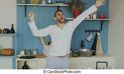 Slow motion of cheerful young funny man dancing and singing with ladle while cooking in the kitchen at home
