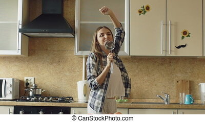 Slow motion of Cheerful young funny woman dancing and singing with ladle while while cooking in the kitchen