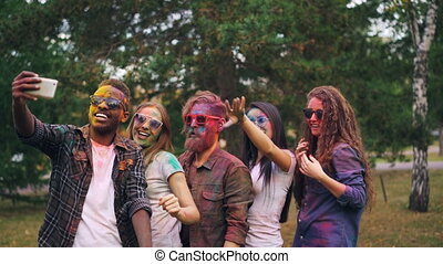 Slow motion of cheerful young people in sunglasses with dirty faces and hair dancing and laughing recording video on smartphone at party taking selfie.
