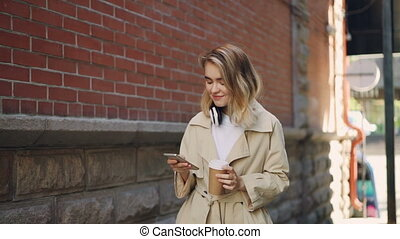 Slow motion of cheerful young woman using smartphone and walking in the street with to-go coffee and headphones. Modern technology, drinks and people concept.