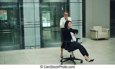 Slow motion of cheerful young women having fun in office...