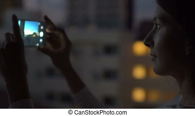 Slow motion of Closeup woman taking photo of cityscape view with smartphone in bar rooftop terrace at night