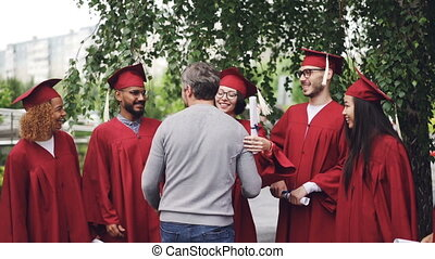 Slow motion of college teacher hugging his students and shaking hands on graduation day with joy and pride. Green trees, educational institution building is visible.