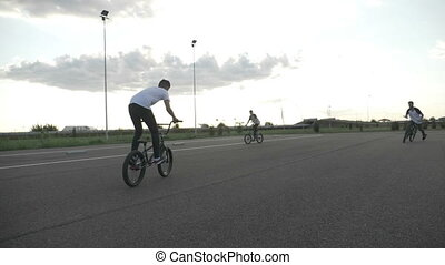 Slow motion of cool bikers on street exercising their freestyle acrobatic tricks