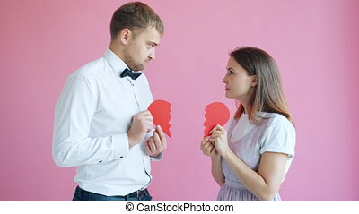 Slow motion of couple dividing heart shape valentine and walking apart holding halves. Romantic relationship, separation and tender feelings concept.
