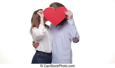 Slow motion of couple playing with a red paper heart and kissing.